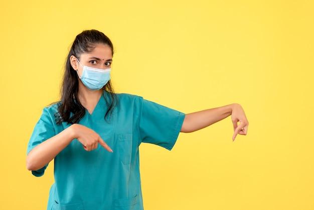 Punto di vista medico femminile affascinante di vista frontale al pavimento su priorità bassa gialla