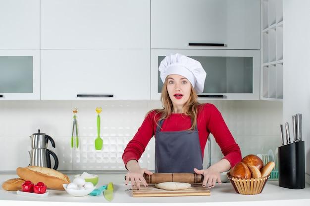 Vista frontale affascinante donna con cappello da cuoco e grembiule che arrotola la pasta in cucina