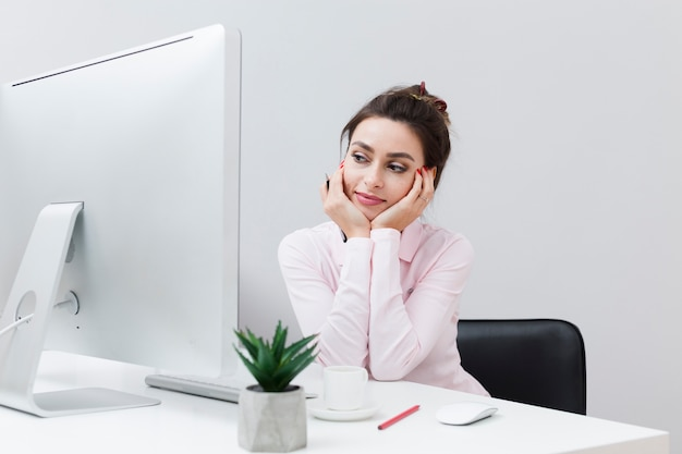 Front view of charming woman working at desk and looking at the computer