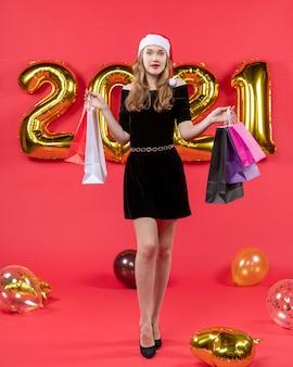 赤のショッピング バッグの風船を保持している黒のドレスを着た魅力的な若い女性の正面図
