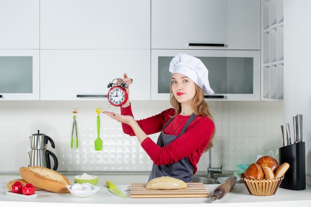 Vista frontale affascinante giovane donna con cappello da cuoco e grembiule che tiene sveglia rossa in cucina