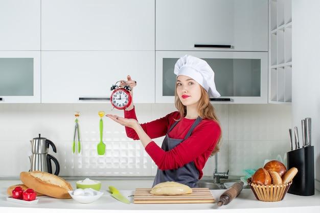 料理の帽子とキッチンで赤い目覚まし時計を保持しているエプロンで魅力的な若い女性の正面図