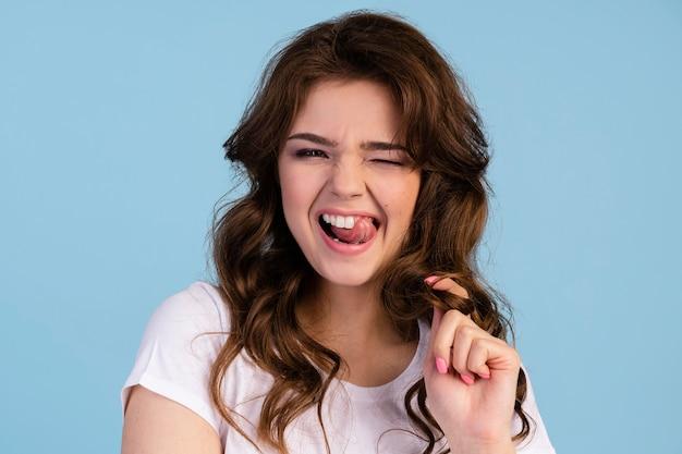 Vista frontale della donna impertinente con le lingue fuori che tocca i suoi capelli