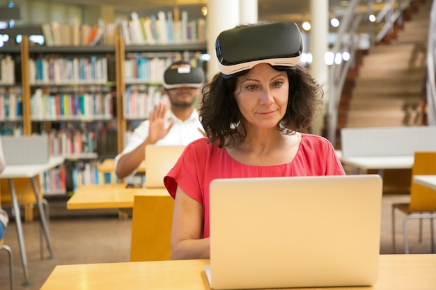 Front view of cheerful caucasian woman setting vr headset