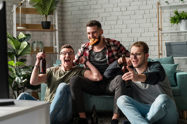 Front view of cheerful male friends having pizza and beer and watching sports on tv