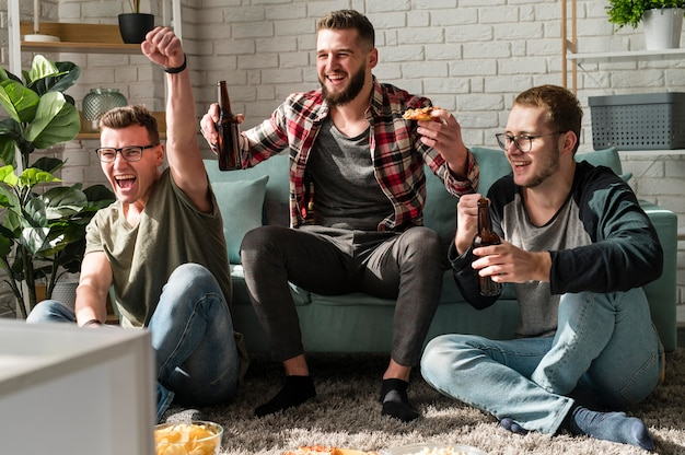 Front view of cheerful male friends having pizza with beer and watching sports on tv