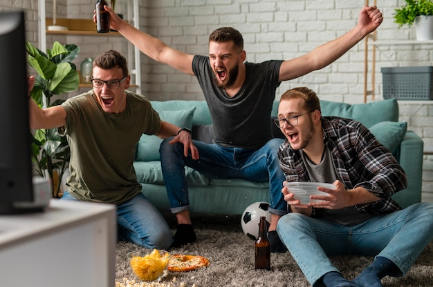 Front view of cheerful male friends watching sports on tv together while having snacks and beer