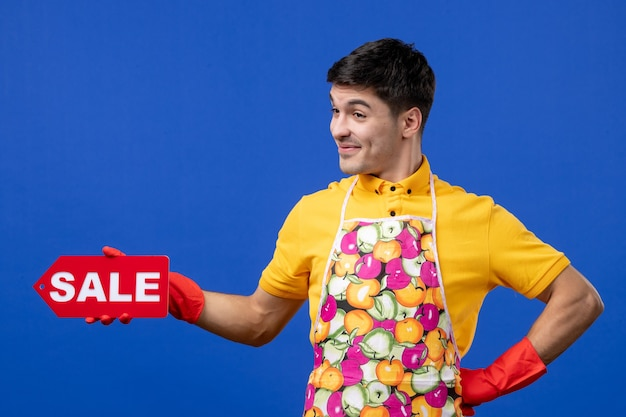 파란색 공간에 허리에 손을 대고 판매 기호를 들고 노란색 티셔츠에 쾌활 한 남성 가정부 전면 보기