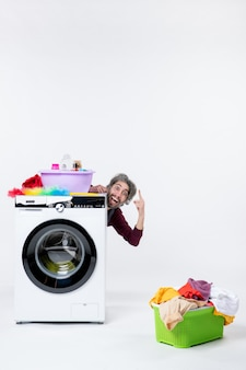 Front view cheerful male housekeeper sitting behind washer laundry basket on white background