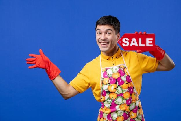 Vista frontale allegra governante maschio con guanti di scarico rossi con cartello di vendita su spazio blu