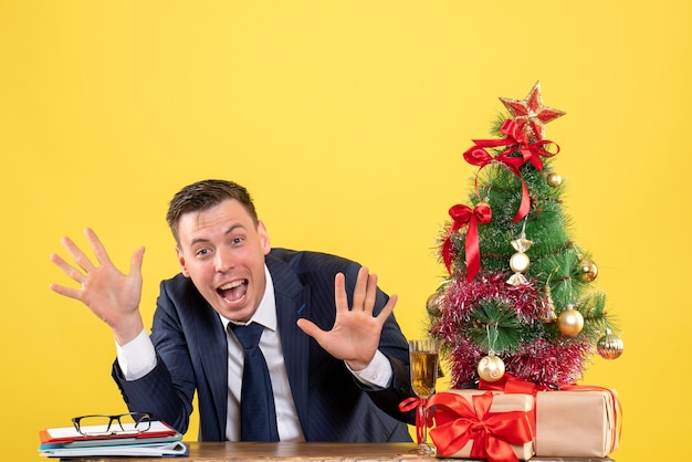 Front view of cheerful man opening hands sitting at the table near xmas tree and presents on yellow