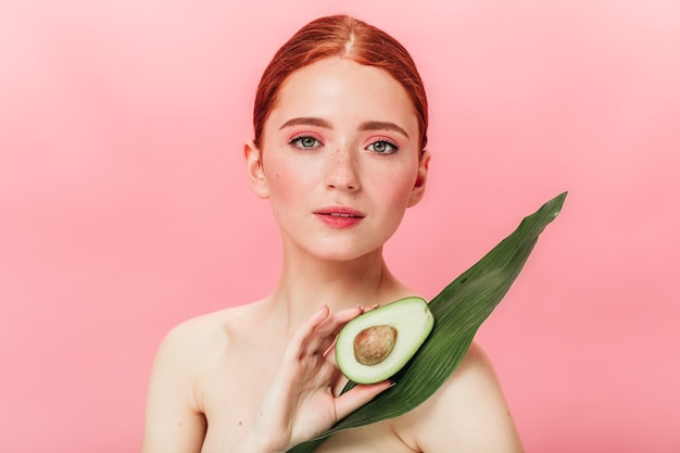 Front view of cheerful nude woman with avocado. ginger girl with healthy food looking at camera.