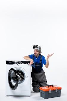 흰색 공간에 손을 올리는 세탁기 근처에 앉아 있는 청진기를 가진 쾌활한 수리공