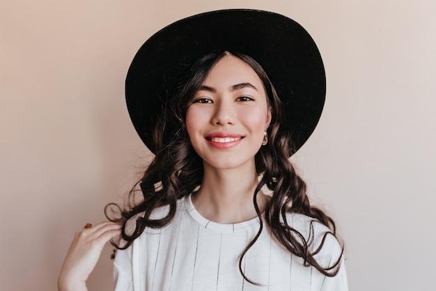 Front view of cheerful smiling asian woman. studio shot of happy korean woman wearing black hat.