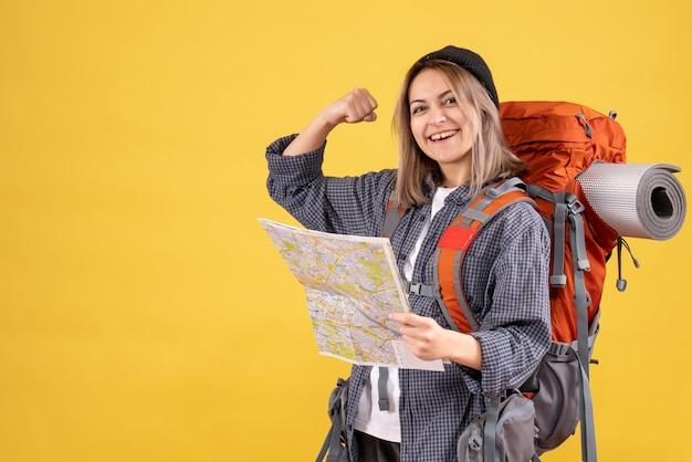 Vista frontale della donna allegra del viaggiatore con la mappa della tenuta dello zaino che mostra il muscolo del braccio