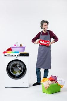 Vista frontale allegro giovane in grembiule che regge il cartello di vendita in piedi vicino alla lavatrice cesto della biancheria su sfondo bianco