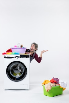 Front view cheerful young man in apron sitting behind washer laundry basket on white background