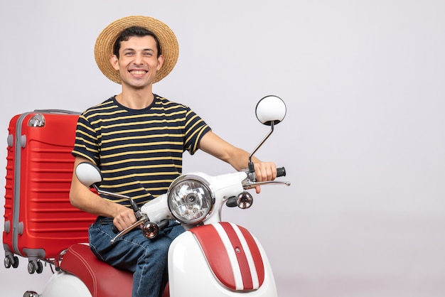 Vista frontale del giovane allegro con la valigia rossa sul ciclomotore
