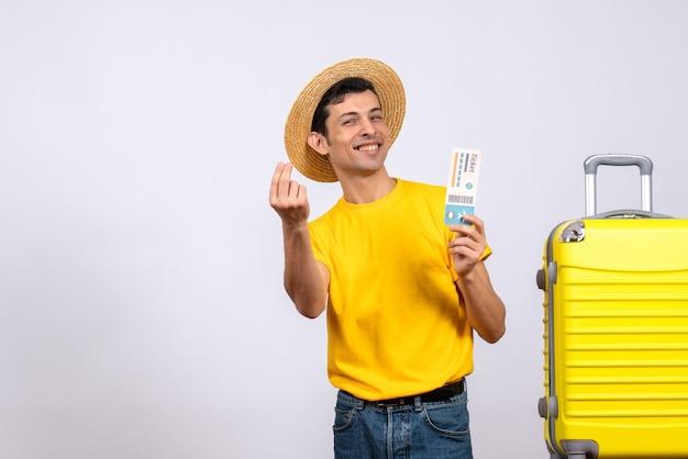 Вид спереди веселый молодой турист в желтой футболке, стоящий возле желтого чемодана