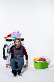 Front view cheery housekeeper man sitting near laundry basket on white background