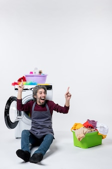 Vista frontale allegra governante maschio seduta davanti al cesto della biancheria della lavatrice su sfondo bianco
