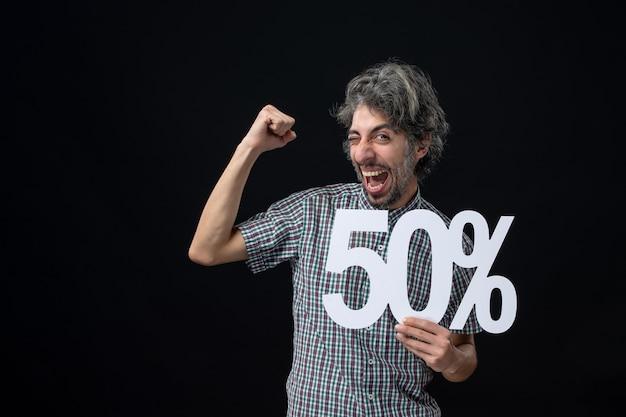 Вид спереди веселый мужчина с выражением победителя, держащий знак на темной стене