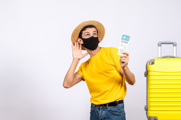 旅行チケットを保持している黄色のスーツケースの近くに立っている黄色のtシャツの正面図陽気な若い男