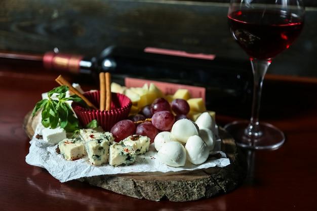 Вид спереди на сырную тарелку микс сыров с виноградом и медом с бокалом красного вина