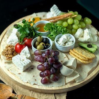 Front view cheese plate on pita bread with grapes olives honey and tomatoes
