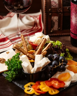 Front view cheese plate with grapes and a glass of red wine
