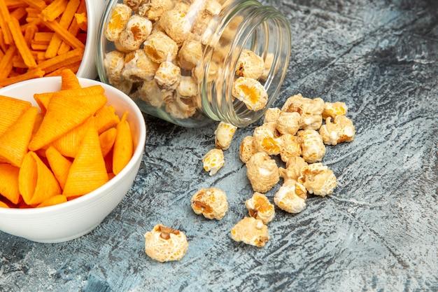 Vista frontale fette biscottate al formaggio con cips e popcorn su sfondo chiaro