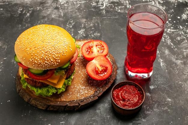 暗い表面のサンドイッチファーストフードパンにジュースと正面図安っぽい肉バーガー