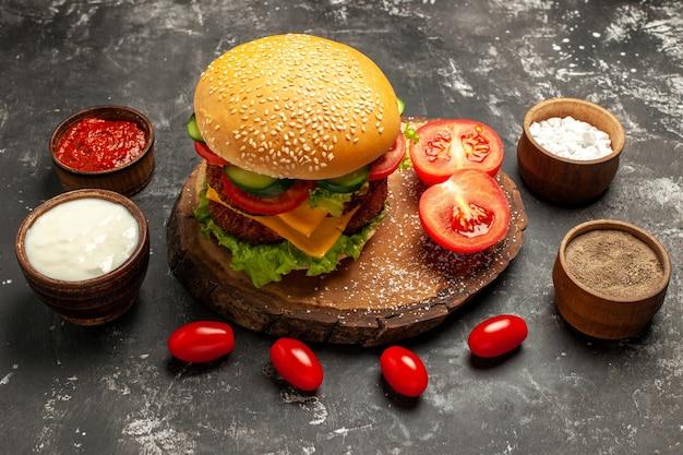 暗い表面のパンサンドイッチミートフライに調味料を入れた正面図の安っぽいミートバーガー