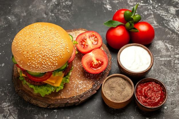 Hamburger di carne di formaggio di vista frontale con pomodori sulla carne di panino patatine fritte panino superficie grigia