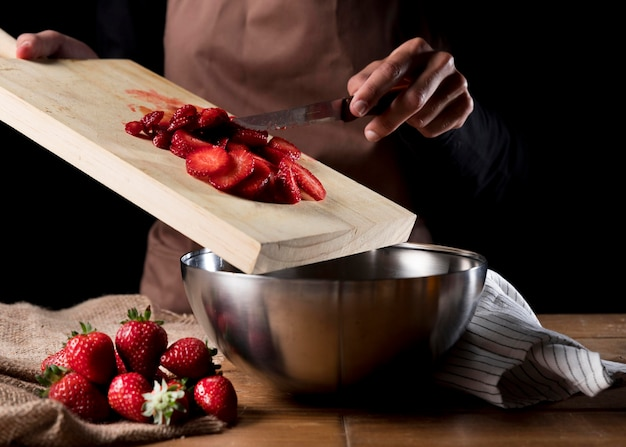 Front view of chef adding chopped strawberries in bowl