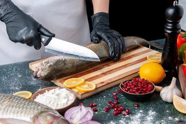 Chef di vista frontale che taglia pesce crudo su tavola di legno macinapepe ciotola di farina semi di melograno in ciotola sul tavolo da cucina