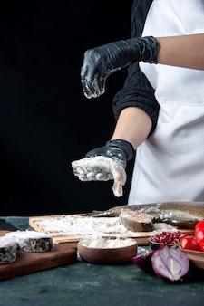 Шеф-повар, вид спереди, покрывает кусочки рыбы мукой на кухонном столе
