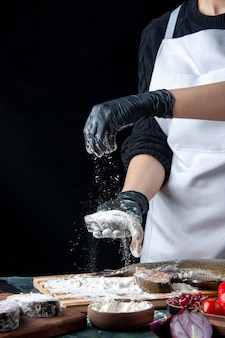 Front view chef covering raw fish slices with flour on kitchen table on black surface
