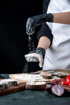 Шеф-повар, вид спереди, покрывает ломтики сырой рыбы мукой на кухонном столе