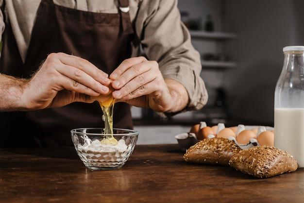 Шеф-повар, взламывающий яйцо, вид спереди