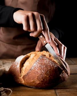 Vista frontale del cuoco unico che taglia pane delizioso