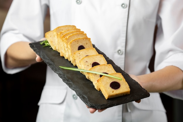 Front view of chef holding a delcious food plate