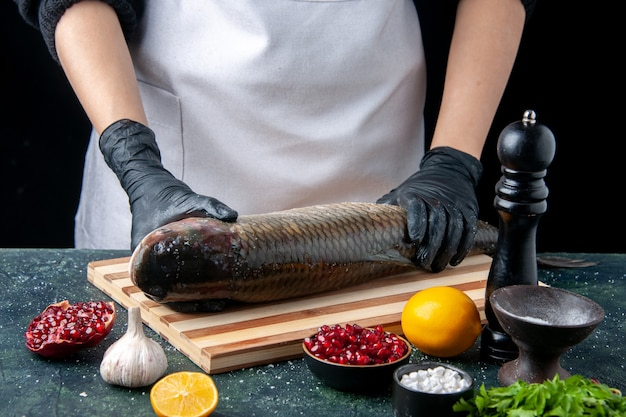 Front view chef in holding raw fish on chopping board pepper grinder pomegranate seeds in bowl on table