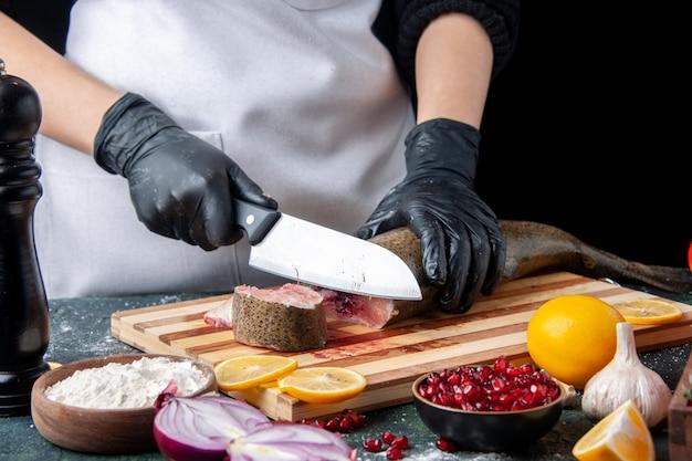 Вид спереди шеф-повар в фартуке, режущий сырую рыбу на разделочной доске, миску для муки на кухонном столе