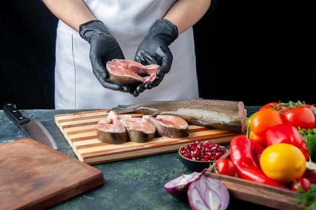 앞치마를 입은 앞치마 요리사가 식탁에 있는 나무 서빙 보드 칼에 생선 조각 야채를 들고 있다