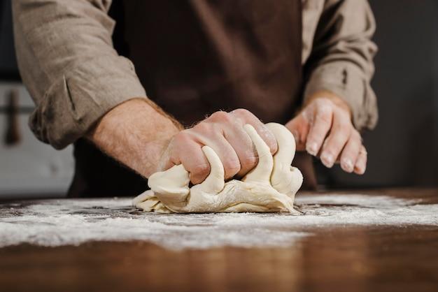 Вид спереди шеф-повар замешивает тесто