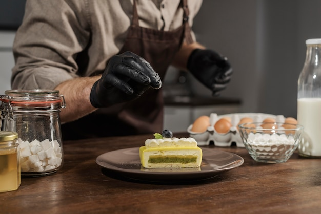 Вид спереди шеф-повар, покрывающий десерт
