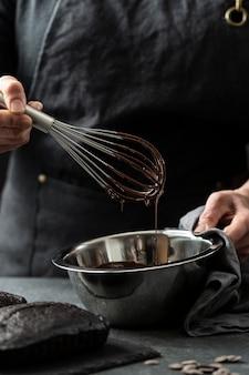 Vista frontale del cuoco unico che prepara la torta al cioccolato