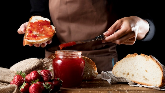 Front view of chef spreading strawberry jam on bread