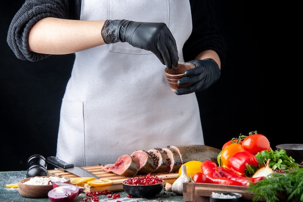 シェフがキッチンテーブルの木製サービングボードのまな板野菜の生の魚のスライスに黒コショウを振りかけた正面図